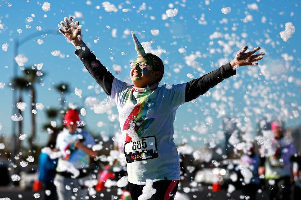 """Aspen Johnson, 12, participates in the Color Run's """"Hero Tour"""" in downtown Las Vegas on Saturday, Feb. 24, 2018. The 5k benefits Three Square Food Bank, which provides wholesome food to the hungry ..."""