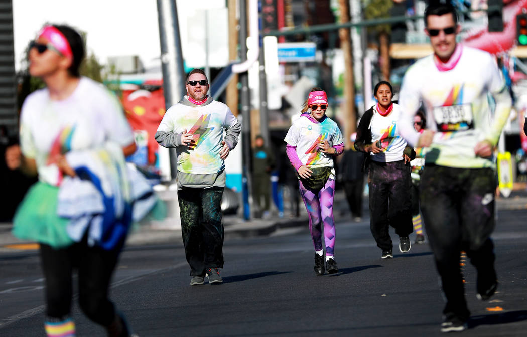 """Bob Glover, second to the left, and his 11-year-old daughter, Peyton, participate in the Color Run's """"Hero Tour"""" in downtown Las Vegas on Saturday, Feb. 24, 2018. The 5k benefits ..."""