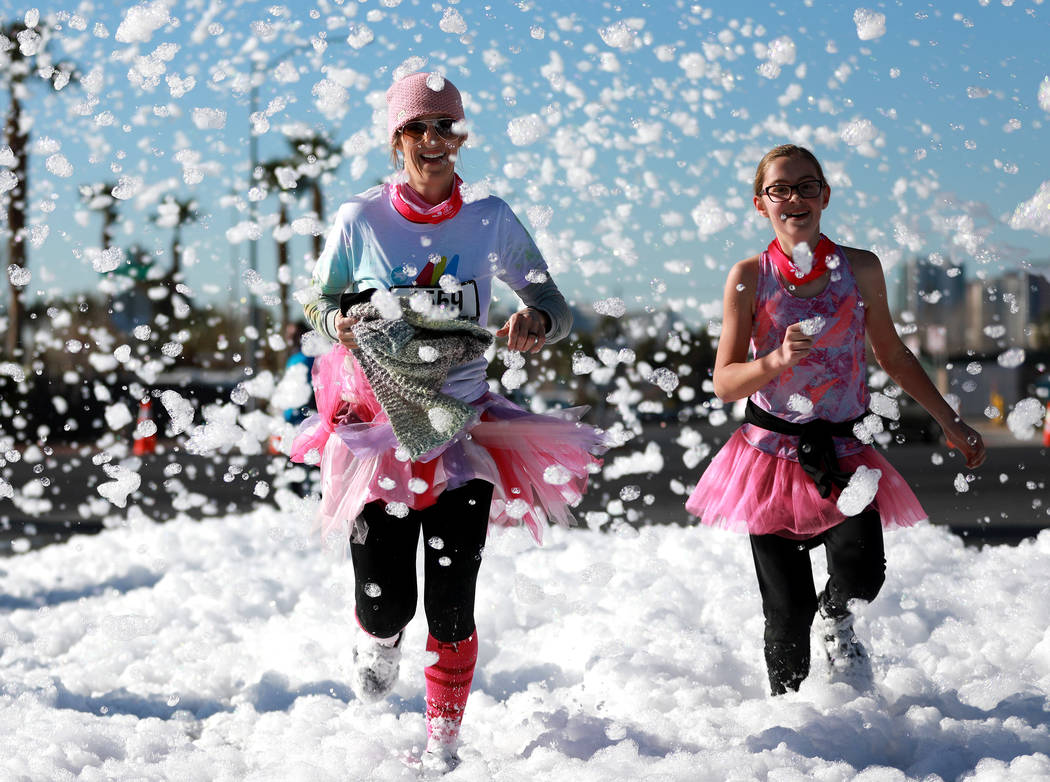 """Participants run in the Color Run's """"Hero Tour"""" in downtown Las Vegas on Saturday, Feb. 24, 2018. The 5k benefits Three Square Food Bank, which provides wholesome food to the hun ..."""
