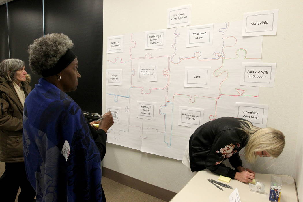 Marian Luke, from left, Parker Philpot and Alexie Ihde of Zappos prepare Post-it notes with suggestions or volunteer offers to put on a puzzle to help solve homelessness during the Mayor's Faith I ...