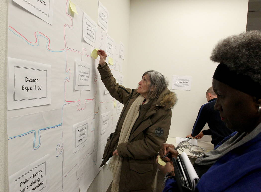 Marian Luke applies Post-it notes to a puzzle with an offer to volunteer to help solve homelessness during the Mayor's Faith Initiative Tiny Home micro Summit at Las Vegas City Hall Thursday, Feb. ...