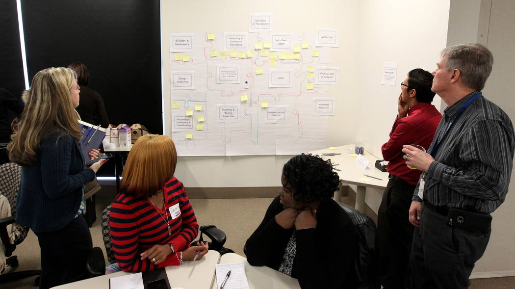 People read Post-it notes meant to fill in pieces of the puzzle to help solve homelessness during the Mayor's Faith Initiative Tiny Home micro Summit at Las Vegas City Hall Thursday, Feb. 22, 2018 ...