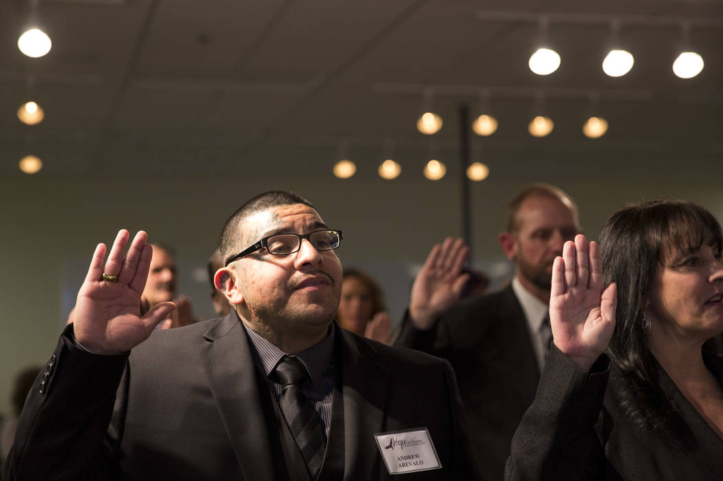 Former gang member Andrew Arevalo, left, and 41 other former and current prisoners are sworn in by District Judge Eric Johnson during the Hope for Prisoners graduation ceremony at the Las Vegas Me ...