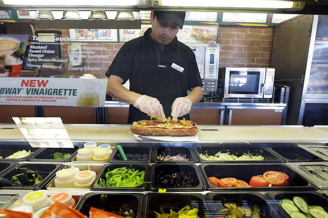 In this March 3, 2015, file photo, Roberto Castelan makes a sandwich at a Subway sandwich franchise in Seattle. Subway is changing up its loyalty program, letting customers earn $2 discounts inste ...