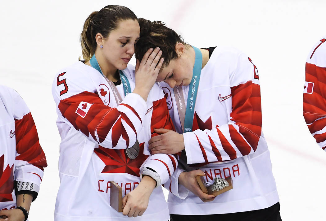 Canada's Lauriane Rougeau (5) comforts forward Rebecca Johnston (6) after losing to the United States in a shootout in the women's gold medal hockey game at the 2018 Winter Olympics in Gangneung,  ...