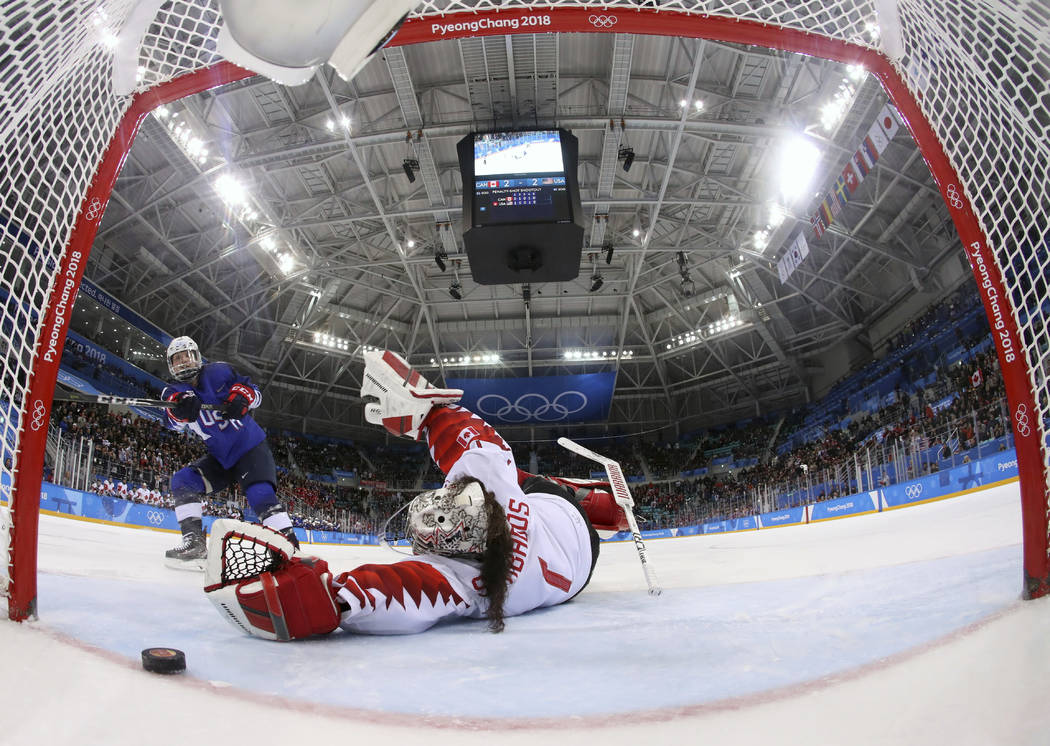 Jocelyne Lamoureux-Davidson (17), of the United States, scores a game winning goal against goalie Shannon Szabados (1), of Canada, in the penalty shootout during the women's gold medal hockey game ...