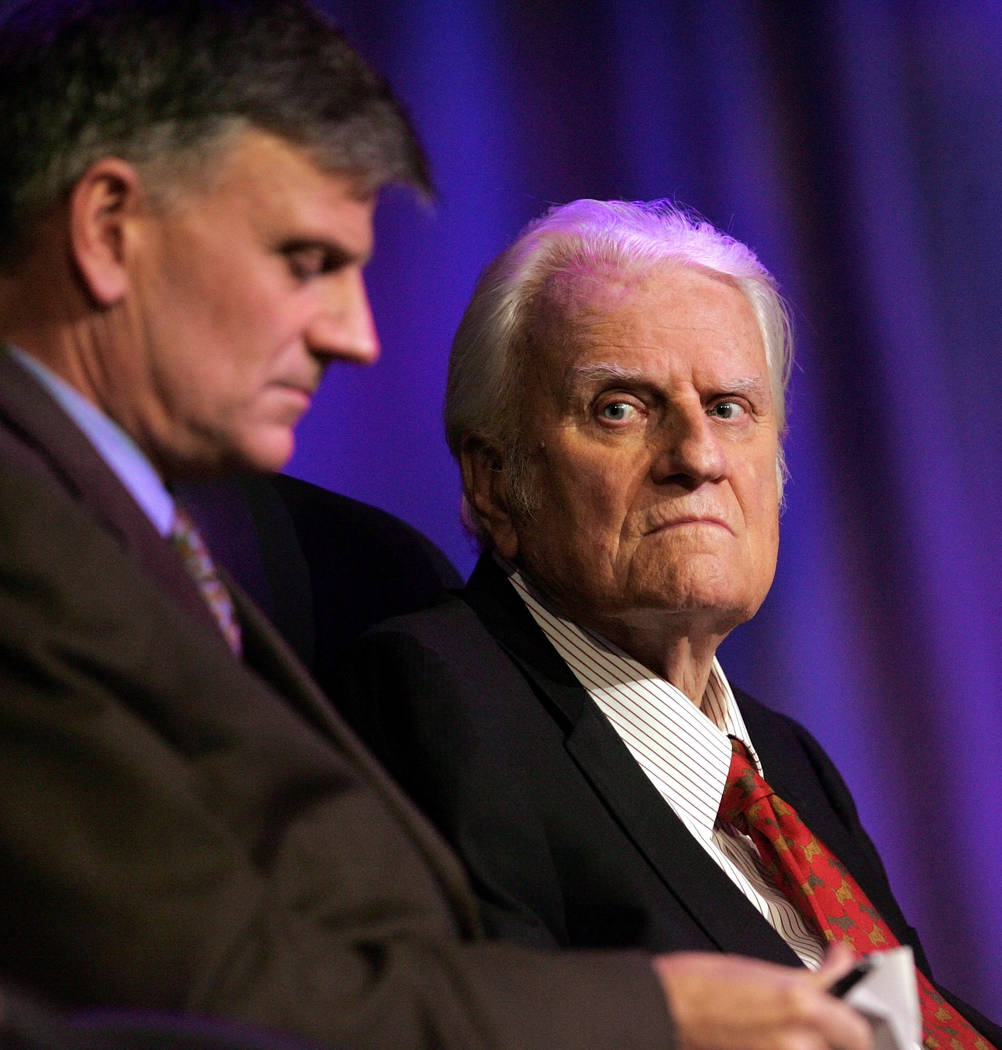Rev. Billy Graham, right, and his son Franklin Graham wait for the start of a service in New Orleans on March 12, 2006. (AP Photo/Bill Haber, File)