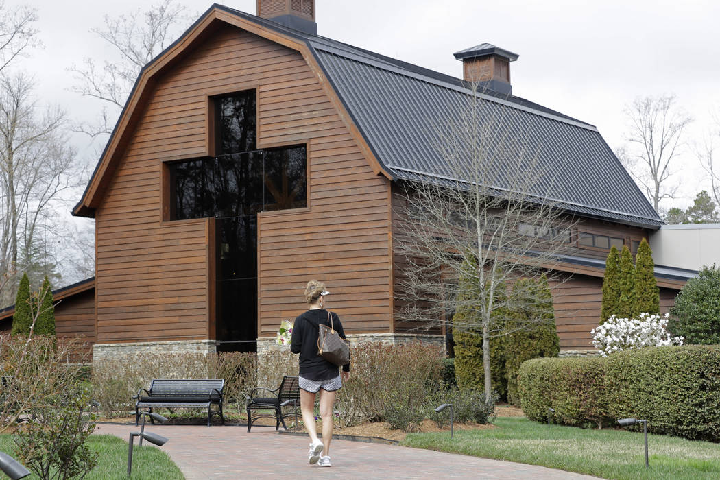 Jo Dockins, of Charlotte, N.C., carries flowers as she visits the Billy Graham Library in Charlotte, N.C., Wednesday, Feb. 21, 2018.  Spokesman Mark DeMoss says Billy Graham, who long suffered fro ...