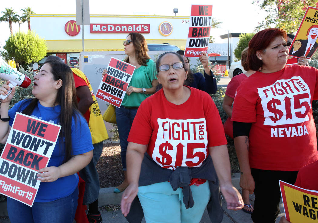 McDonald's franchise employees, including Diana Diaz, center, and Lupe Guzman, right, protest for a higher minimum wage outside of a McDonald's on 2650 W. Sahara Ave., on Wednesday, May 24, 2017,  ...