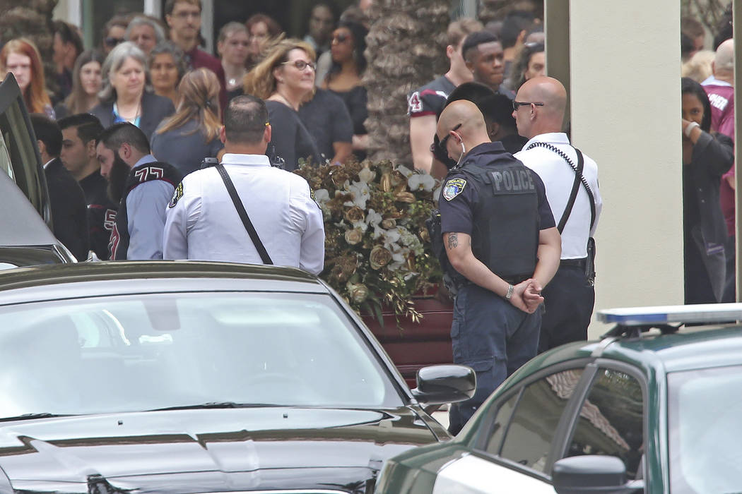 The flower draped casket carrying the body of Aaron Feis, who was killed at Marjory Stoneman Douglas High School, departs the Church by the Glades Thursday, Feb. 22, 2018, in Coral Springs, Fla. ( ...