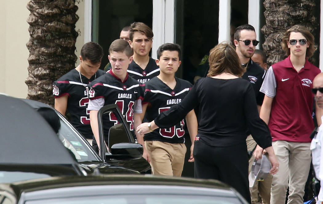 Members of the Marjory Stoneman Douglas High School football team depart the service at the Church by the Glades for Aaron Feis, the football coach who was killed at the school shooting last week, ...