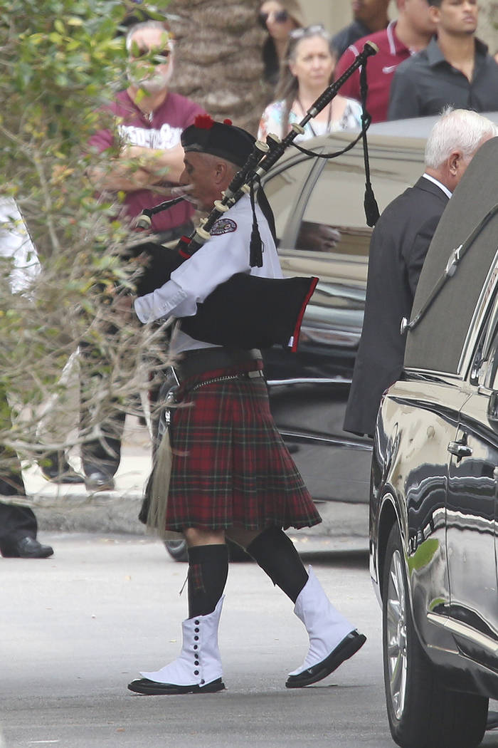 A  bagpiper leads the casket carrying the body of Aaron Feis, who was killed at Marjory Stoneman Douglas High School, at the Church by the Glades Thursday, Feb. 22, 2018, in Coral Springs, Fla. (A ...