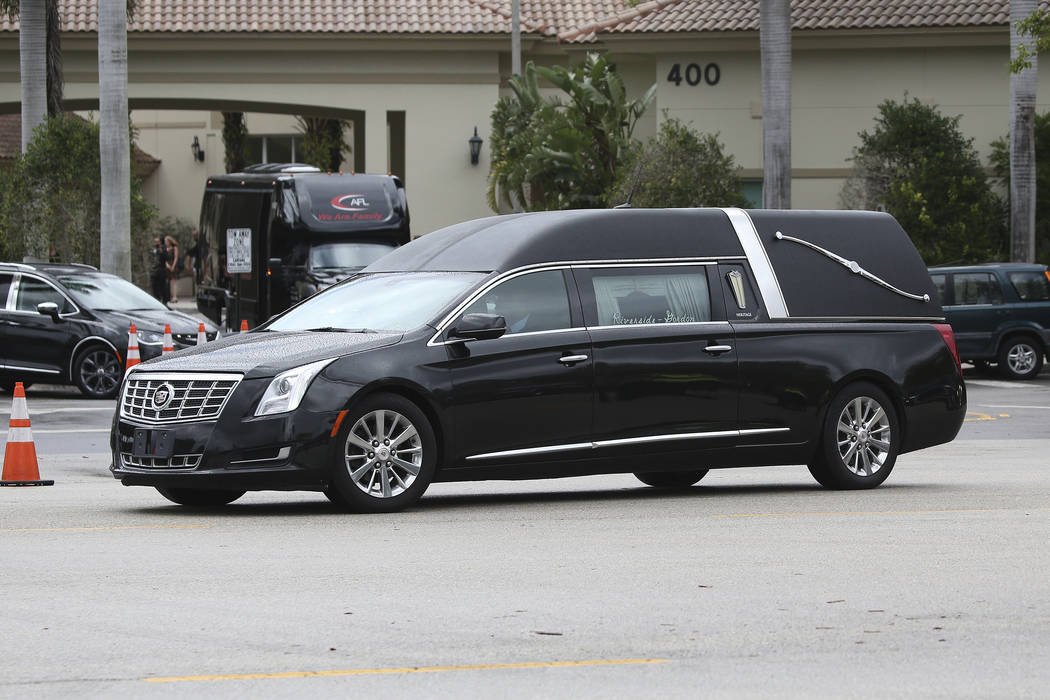 The hearse carrying the body of Aaron Feis the football coach who was killed at Marjory Stoneman Douglas High School departs the Church by the Glades Thursday, Feb. 22, 2018, in Coral Springs, Fla ...
