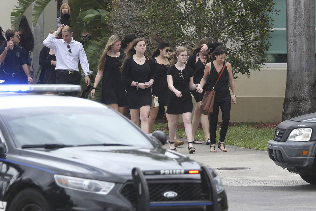 Mourners depart the Church by the Glades, where the funeral for Aaron Feis,who was killed at Marjory Stoneman Douglas High School was held Thursday, Feb. 22, 2018, in Coral Springs, Fla. (AP Photo ...