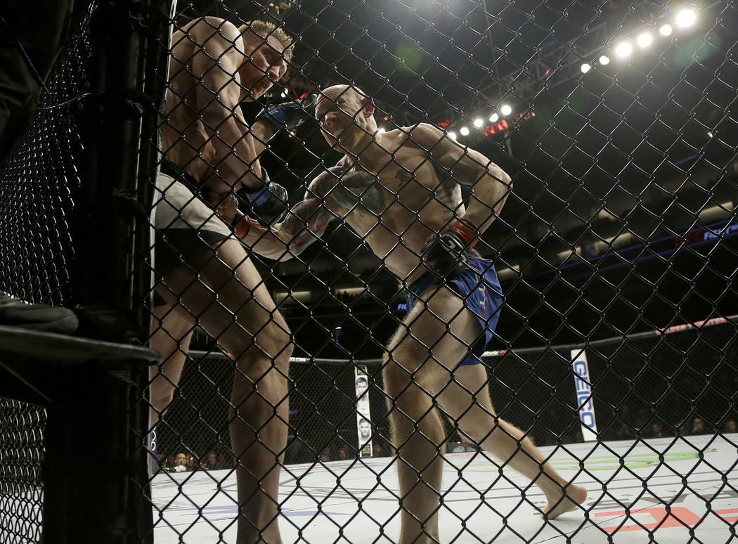 Josh Emmett, right, punches Scott Holtzman during a UFC Fight Night mixed martial arts fight in Sacramento, Calif., Saturday, Dec. 17, 2016. (AP Photo/Jeff Chiu)