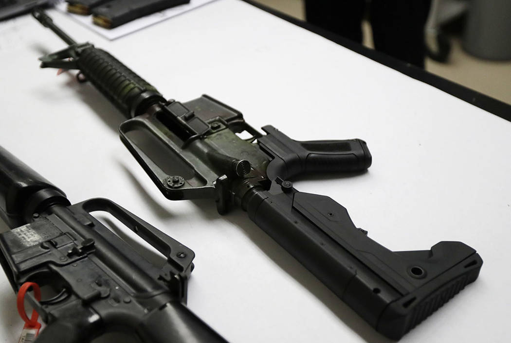 A semi-automatic rifle, at right, that has been fitted with a bump stock device sits on a table at the Washington State Patrol crime laboratory in Seattle. (AP Photo/Ted S. Warren)