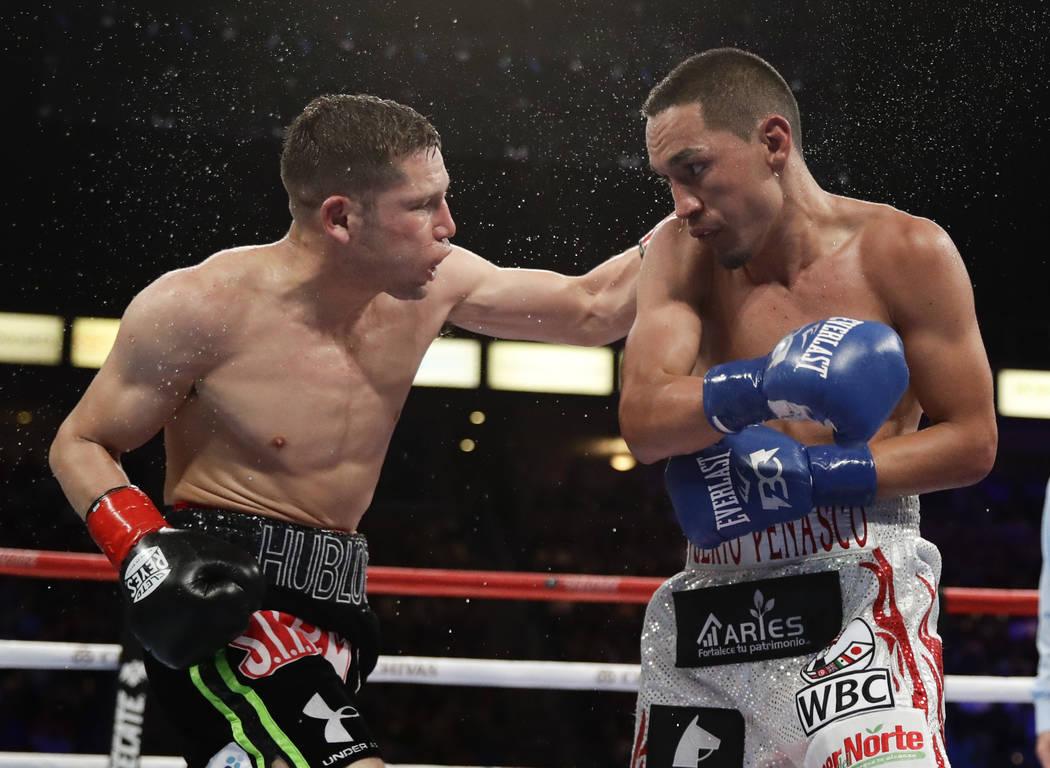 Carlos Cuadras, left, of Mexico, hits Juan Francisco Estrada, of Mexico, during their WBC super flyweight title boxing match Saturday, Sept. 9, 2017, in Carson, Calif. (AP Photo/Chris Carlson)