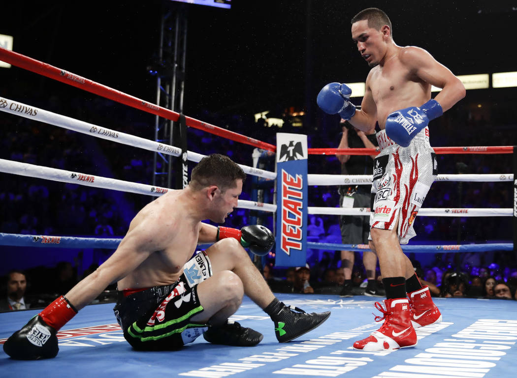 Juan Francisco Estrada, right, of Mexico, knocks down Carlos Cuadras, of Mexico, during the 10th round during their WBC super flyweight title boxing match Saturday, Sept. 9, 2017, in Carson, Calif ...
