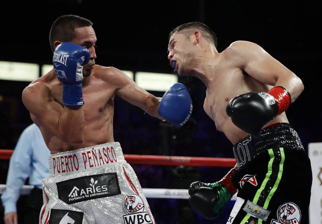 Juan Francisco Estrada, left, of Mexico, hits Carlos Cuadras, of Mexico, during the 10th round during their WBC super flyweight title boxing match Saturday, Sept. 9, 2017, in Carson, Calif. (AP Ph ...