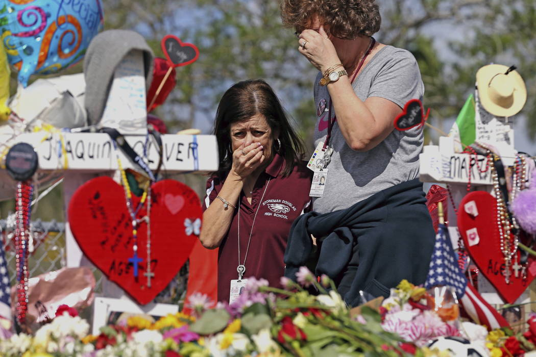 Marjory Stoneman Douglas High School administrative employees Margarita LaSalle, left, and JoEllen Berman, walk along the hill near the school lined with 17 crosses to honor the students and teach ...
