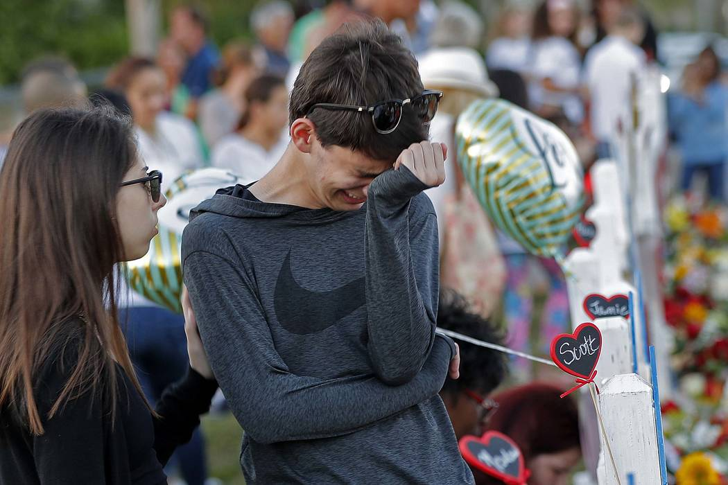 Daniel Bishop, 16, a student at Marjory Stoneman Douglas High School, cries at a makeshift memorial outside the school, in Parkland, Fla., Sunday, Feb. 18, 2018.  (Gerald Herbert/AP)