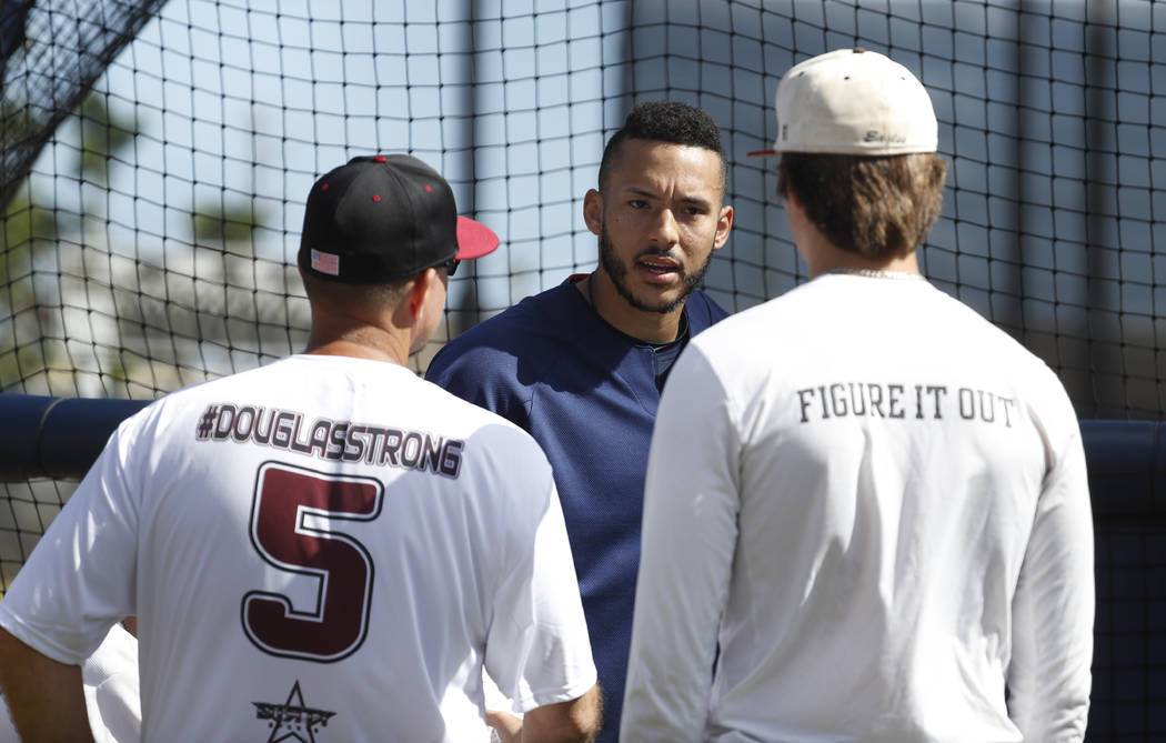 Houston Astros shortstop Carlos Correa chats with Douglas Stoneman High School's baseball head coach Todd Fitz-Gerald, left, and his son, Hunter Fitz-Gerald, right, during baseball spring training ...