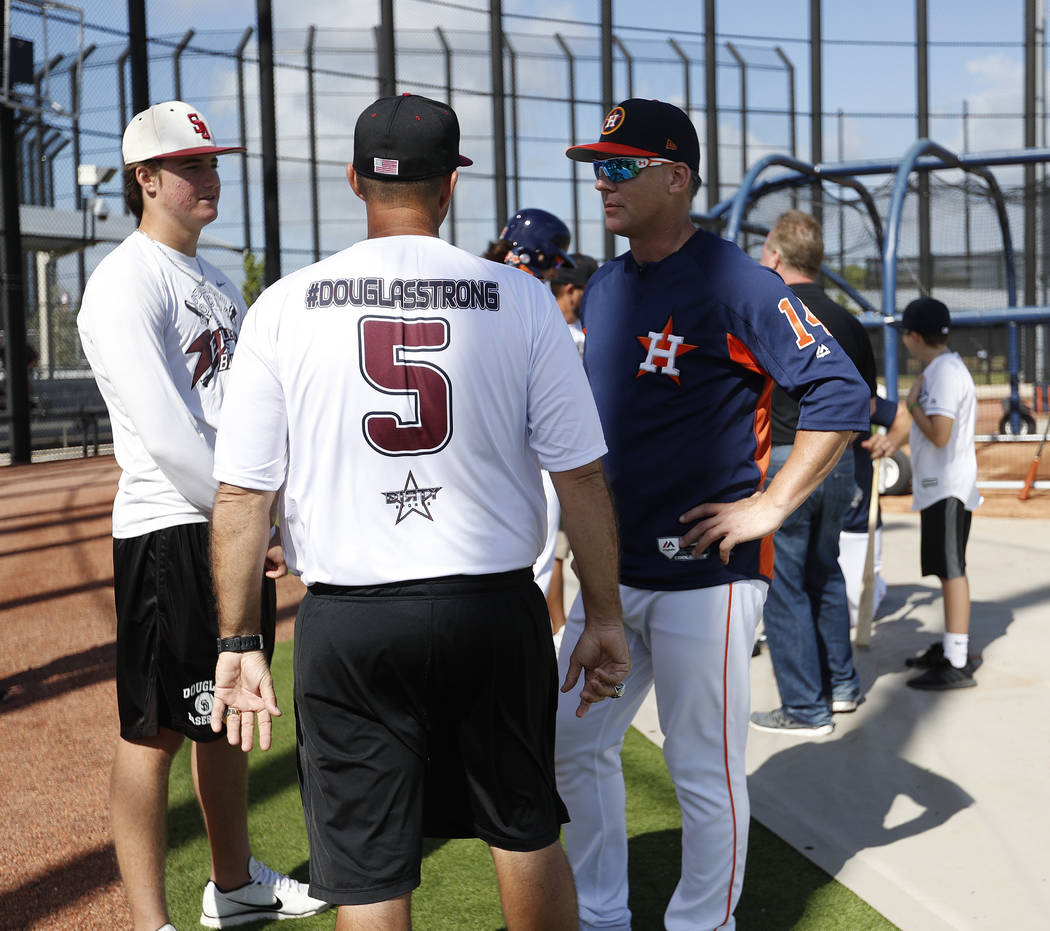 Houston Astros manager A.J. Hinch talks with Douglas Stoneman High School's baseball head coach Todd Fitz-Gerald, center, and his son, Hunter Fitz-Gerald, left, during baseball spring training in  ...