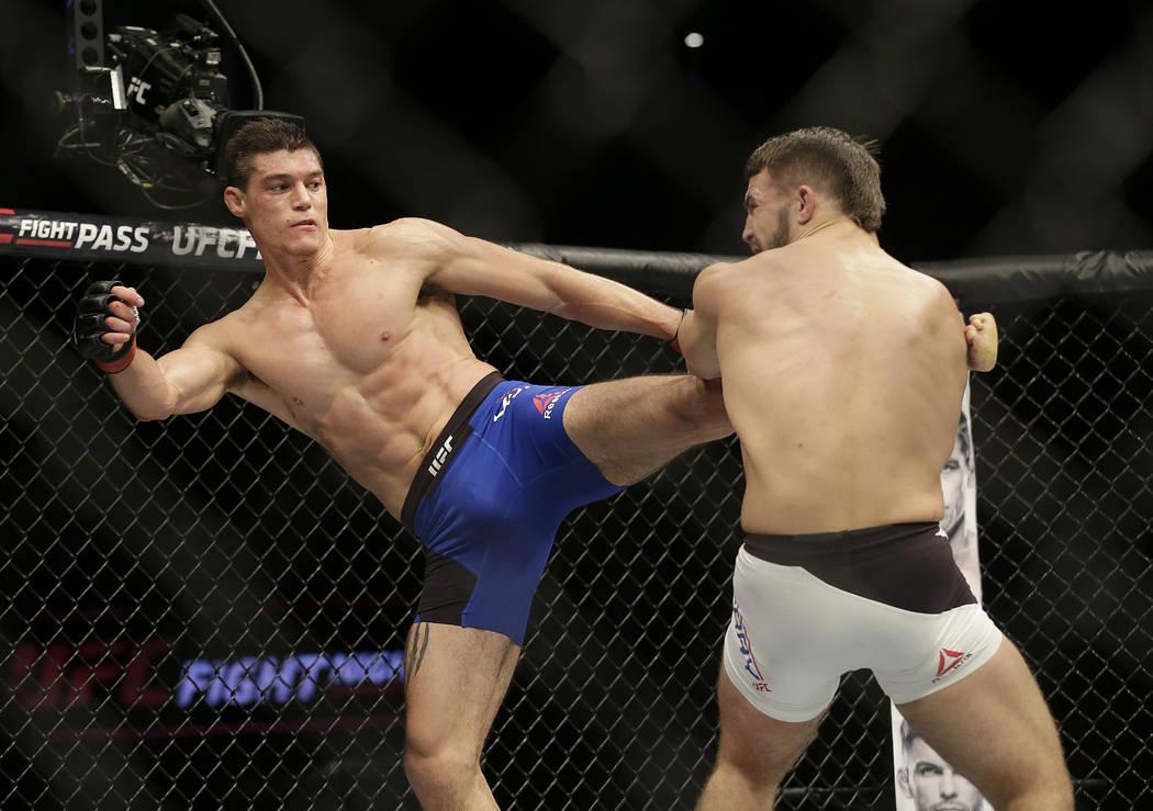 Alan Jouban, left, kicks Mike Perry during a UFC Fight Night mixed martial arts fight in Sacramento, Calif., Saturday, Dec. 17, 2016. (AP Photo/Jeff Chiu)