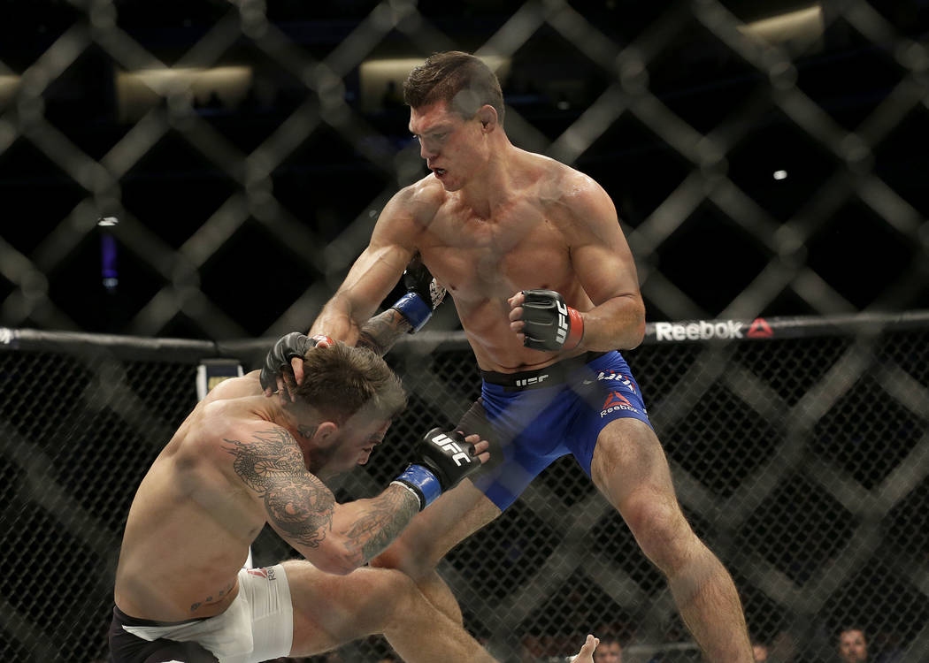 Alan Jouban, top, fights Mike Perry during a UFC Fight Night mixed martial arts fight in Sacramento, Calif., Saturday, Dec. 17, 2016. (AP Photo/Jeff Chiu)