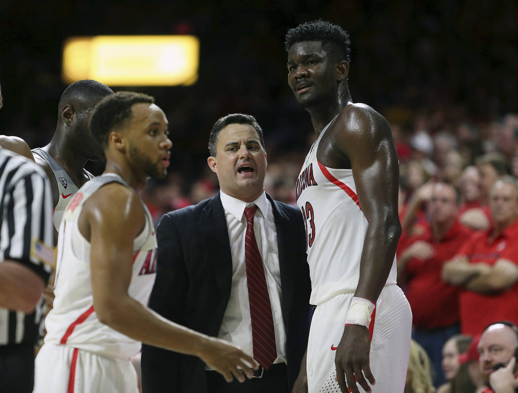 Arizona head coach Sean Miller, center, talks with forward Deandre Ayton (13) during the second half of an NCAA college basketball game against Arizona State, Saturday, Dec. 30, 2017, in Tucson, A ...