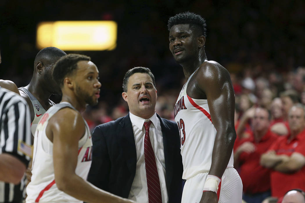 Arizona head coach Sean Miller, center, talks with forward Deandre Ayton, right, during the second half of an NCAA college basketball game against Arizona State, Saturday, Dec. 30, 2017, in Tucson ...