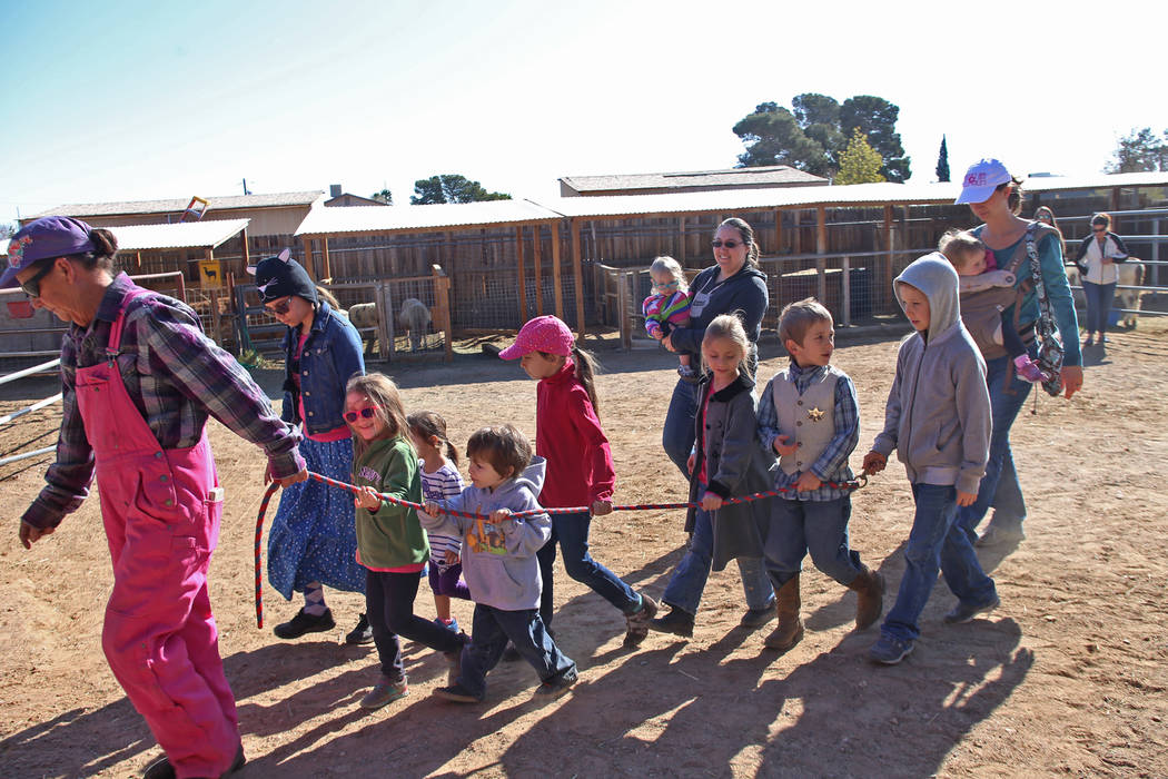 Kathleen Meehan leads children out of the area to form a line for pony rides at J.R. Pony Farm in Las Vegas, Wednesday, Feb. 28, 2018. The city of Las Vegas wants to annex 872 acres of land that w ...