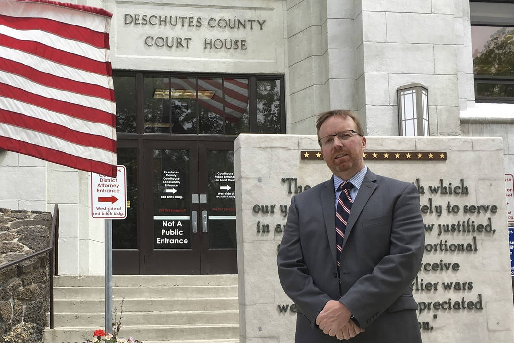 Deschutes County District Attorney John Hummel stands in front of the county courthouse in Bend, Ore., in 2016.  (AP Photo/Andrew Selsky)