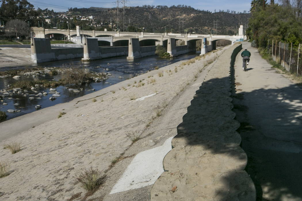 A cyclist rides along recently installed temporary flood control walls along the low level L.A. River in Los Angeles in 2016. (AP Photo/Damian Dovarganes, File)