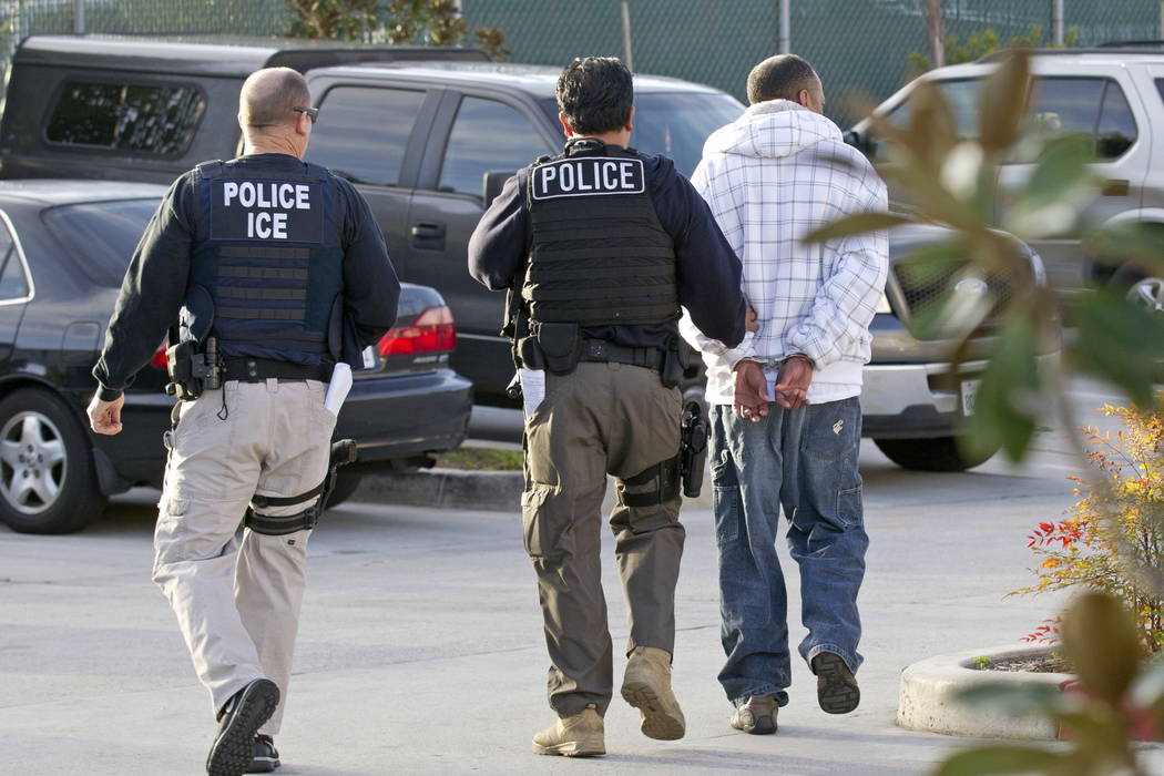 Immigration and Customs Enforcement (ICE) agents take a suspect into custody as part of a nationwide immigration sweep in Chula Vista, Calif., in 2012. (AP Photo/Gregory Bull, File)