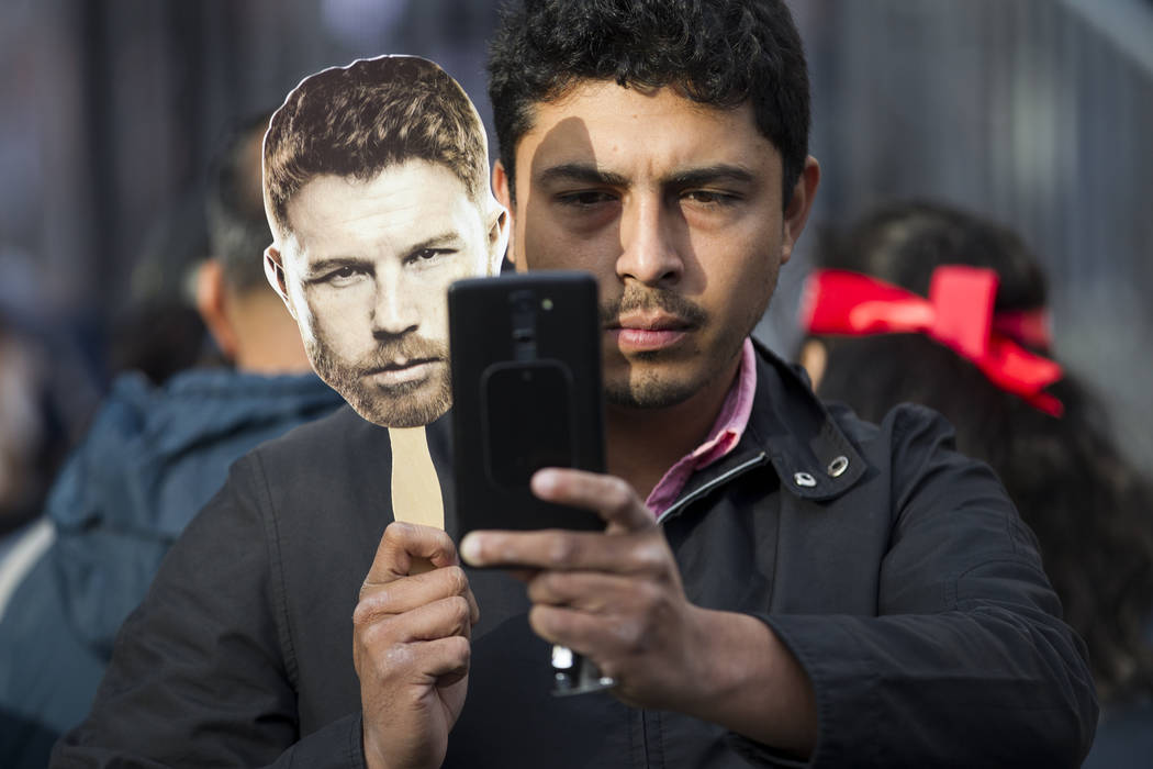 """Vicente Mijares of Mexico takes a photo with a face cutout of Saul """"Canelo"""" Alvarez during a boxing press conference at Microsoft Square in Los Angeles, Calif., Tuesday, Feb. 27, 2018. E ..."""