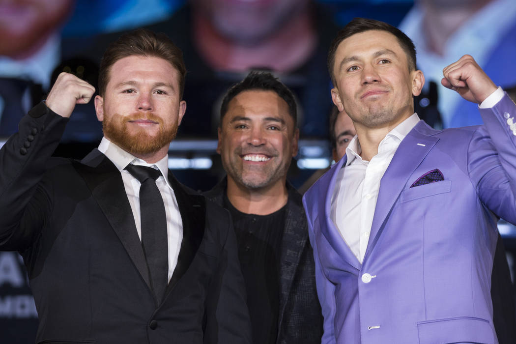 """Boxers Saul """"Canelo"""" Alvarez, left, and Gennady Golovkin, right, during their press conference with boxing promoter Oscar De La Hoya, at Microsoft Square in Los Angeles, Calif., Tuesday, ..."""