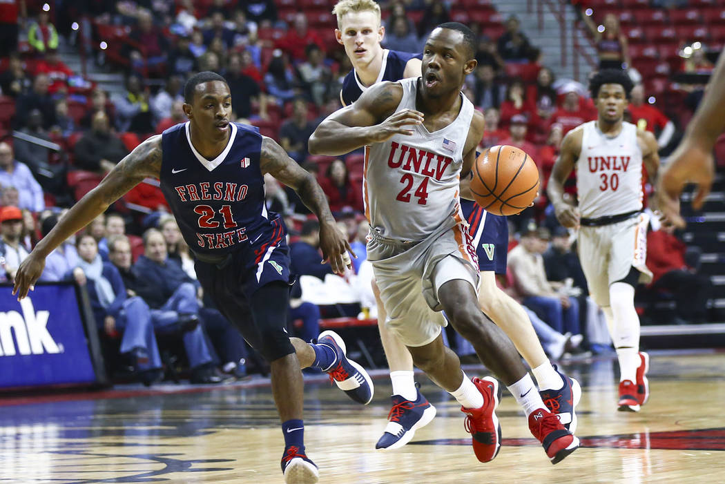 UNLV Rebels guard Jordan Johnson (24) drives against Fresno State Bulldogs guard Deshon Taylor (21) during the first half of a basketball game at the Thomas & Mack Center in Las Vegas on Wedne ...