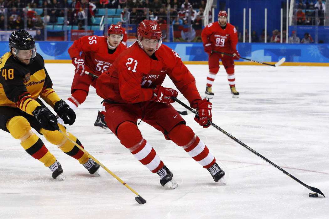 Russian athlete Sergey Kalinin (21) tries to get past Frank Hordler (48), of Germany, during the first period of the men's gold medal hockey game at the 2018 Winter Olympics, Sunday, Feb. 25, 2018 ...