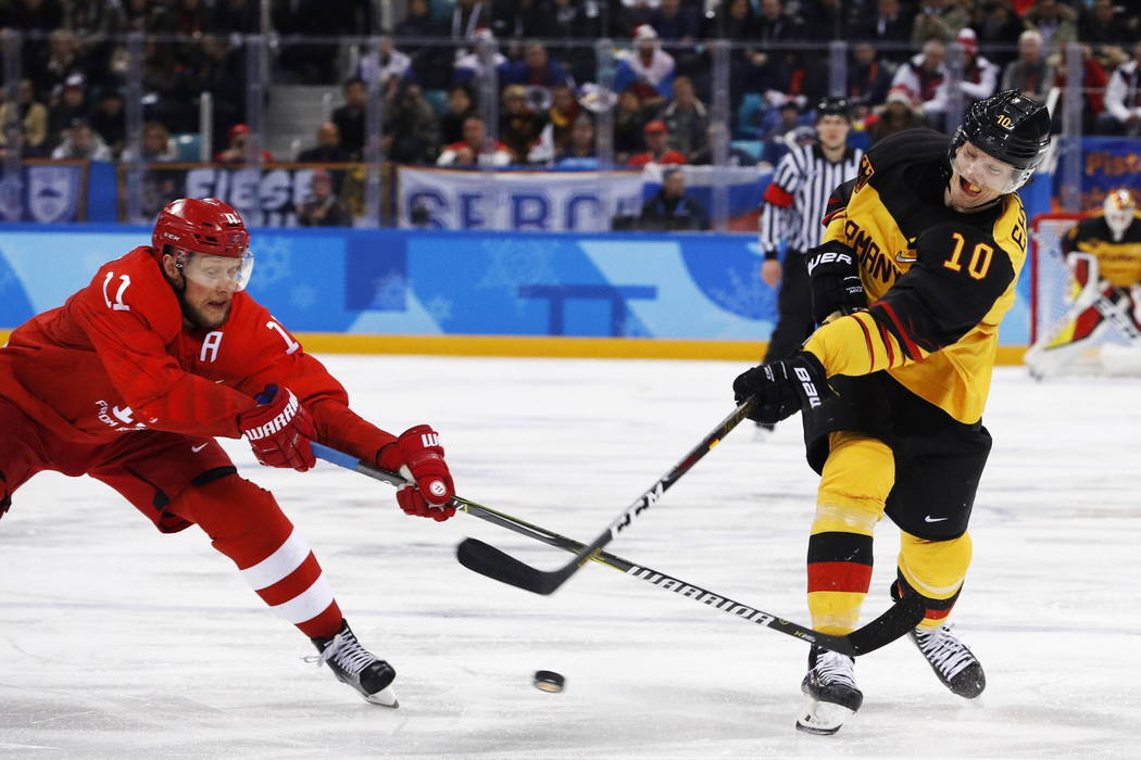 Christian Ehrhoff (10), of Germany, shoots the puck against Russian athlete Sergei Andronov (11) during the second period of the men's gold medal hockey game at the 2018 Winter Olympics, Sunday, F ...