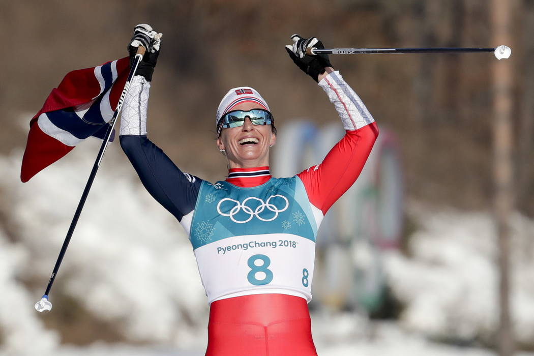 Marit Bjoergen, of Norway, celebrates after winning the gold medal in the women's 30k cross-country skiing competition at the 2018 Winter Olympics in Pyeongchang, South Korea, Sunday, Feb. 25, 201 ...