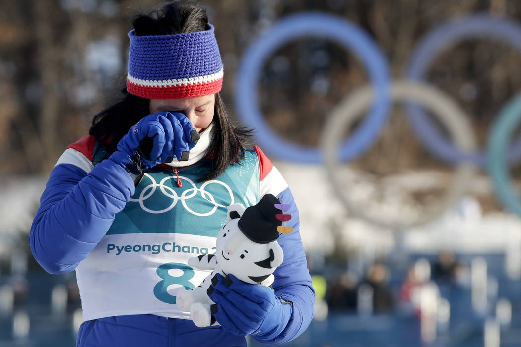 Marit Bjoergen, of Norway, wipes a tear away after winning the gold medal in the women's 30k cross-country skiing competition at the 2018 Winter Olympics in Pyeongchang, South Korea, Sunday, Feb.  ...