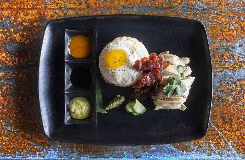 Hainanese chicken rice with Mary's free range chicken, chicken schmaltz rice, organic fried egg, Chinese sausage, cucumbers,, pickled mustard, greens, ginger scallion sauce, house made chili and h ...