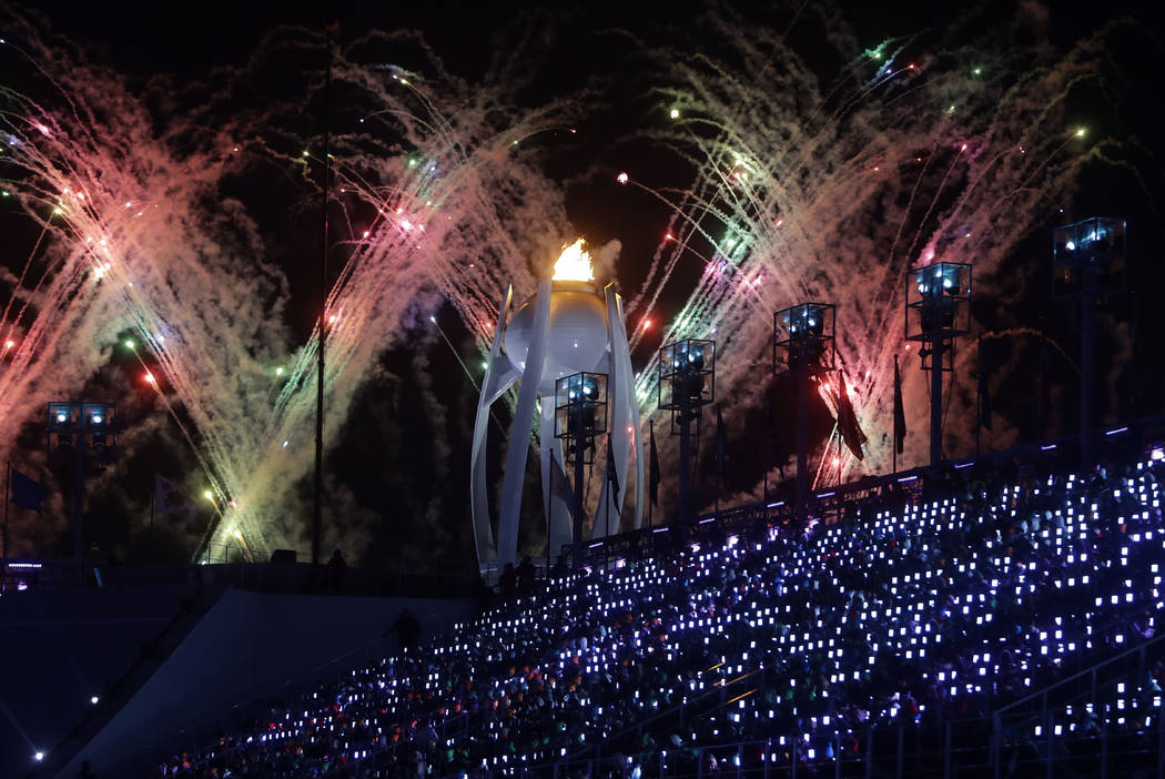 Fireworks explode over the Olympic flame during the closing ceremony of the 2018 Winter Olympics in Pyeongchang, South Korea, Sunday, Feb. 25, 2018. (AP Photo/Michael Probst)