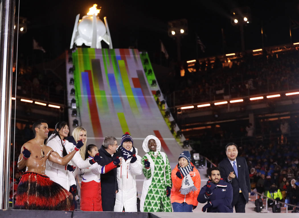 Athletes from various nations including Pita Taufatofua, of Tonga, at left, United States' Lindsey Vonn, third from left, and Thomas Bach, president of the International Olympic Committee, fifth f ...