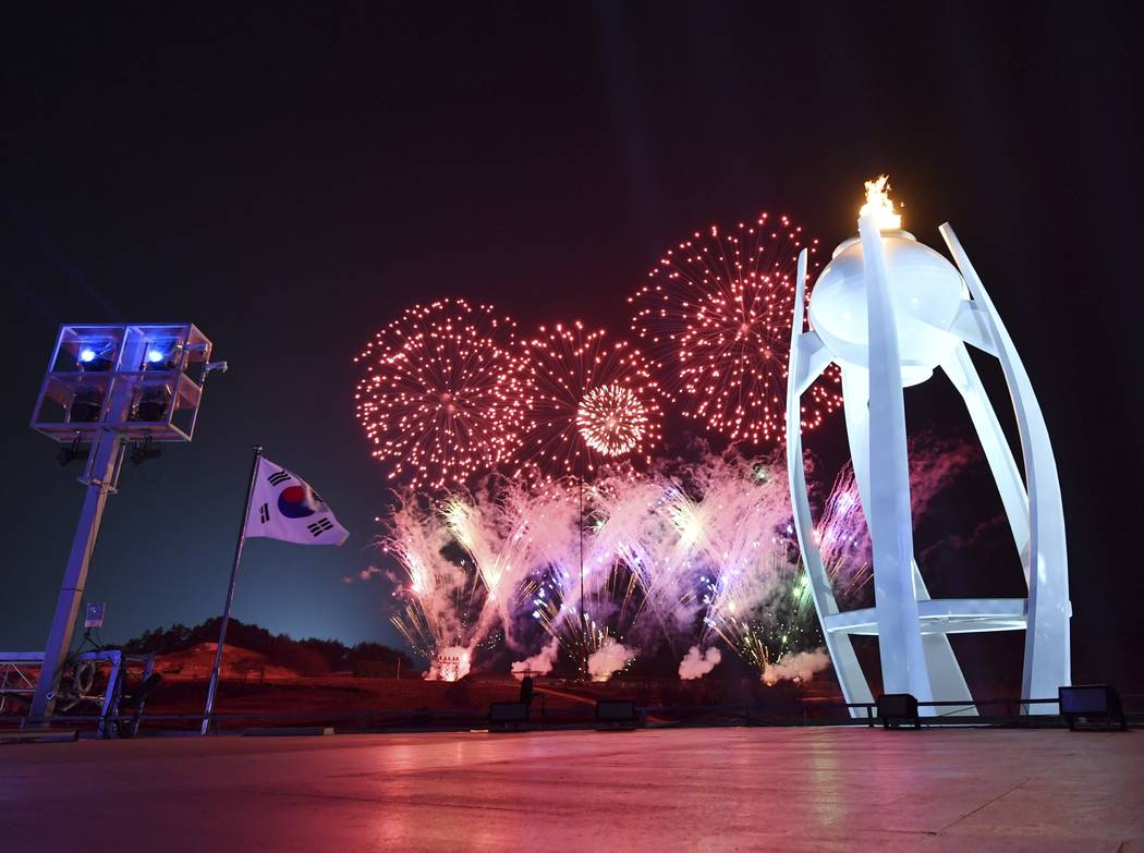 Fireworks explode behind the Olympic cauldron during the closing ceremony of the 2018 Winter Olympics in Pyeongchang, South Korea, Sunday, Feb. 25, 2018. (Florien Choblet/Pool Photo via AP)