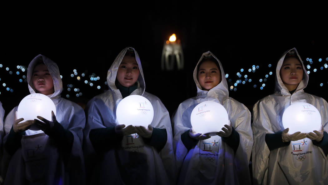 Performers carry lights during the closing ceremony of the 2018 Winter Olympics in Pyeongchang, South Korea, Sunday, Feb. 25, 2018. (AP Photo/Natacha Pisarenko)