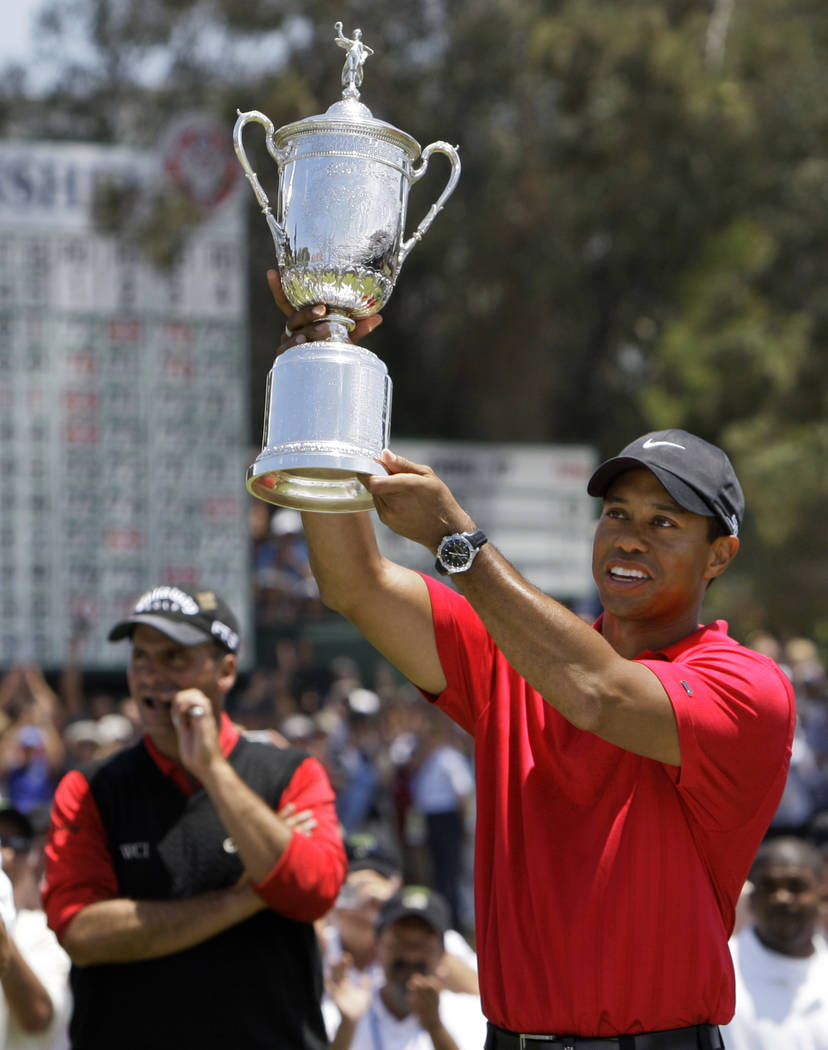 In this June 16, 2008, file photo, Tiger Woods holds up the championship trophy after winning the U.S. Open against Rocco Mediate, left, after a sudden death hole following an 18-hole playoff roun ...
