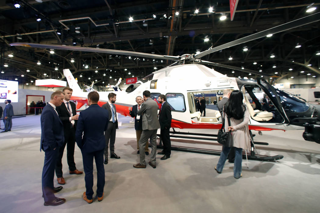 Exhibitgoers watch the AW109, a lightweight, twin-engine, eight-seat multi-purpose helicopter developed and manufactured by the Leonardo's Helicopter Division, during the 2018 International Helico ...