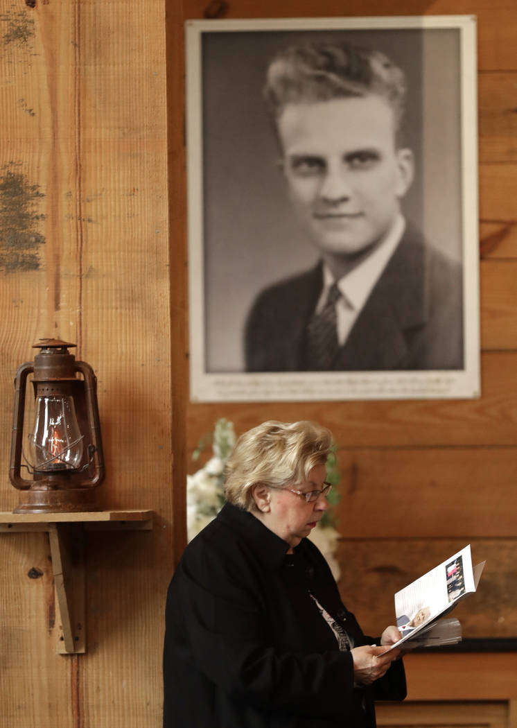 A woman reads a brochure under a large photo of Billy Graham as she pays respects to Billy Graham during a public viewing at the Billy Graham Library in Charlotte, N.C., Monday, Feb. 26, 2018. (AP ...